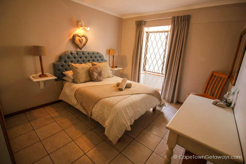 Beautiful bedroom with queen-size bed covered with caramel coloured bedding